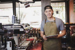Junger Mann steht hinter der Theke in einem Cafe
