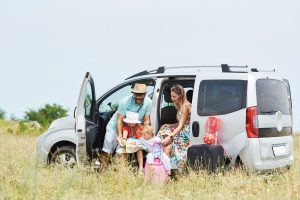 Familie steht an offenem Auto mit Kinder