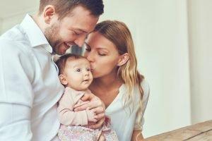 Vater und Mutter haben ein Baby auf dem Arm