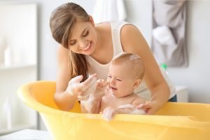 mutter badet ihr kleines baby in einer wanne