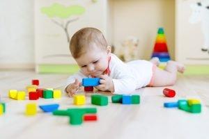 kleines baby spielt mit bunten baukloetzen