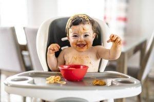 ein kleines Mädchen verteilt das Essen auf dem gesamten Körper
