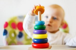 Baby spielt ein Spiel mit Holzklötzen