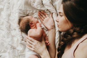 mutter liegt mit ihrem neugeborenen im bett