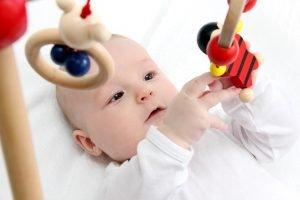 baby spielt in rueckenlage mit spielzeugen