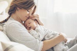 junge mutter haelt ihr baby im arm