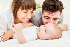 glueckliche eltern kuscheln mit ihrem baby