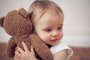 baby kuschelt mit einem teddybaer