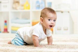 neugieriges baby krabbelt ueber den boden