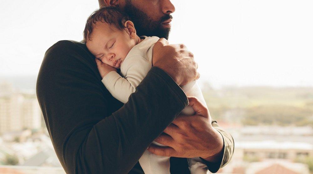 vater hält baby im arm