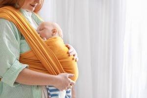 junge mutter mit ihrem kind in einem tragetuch