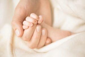 mutter haelt die hand ihres neugeborenen babys