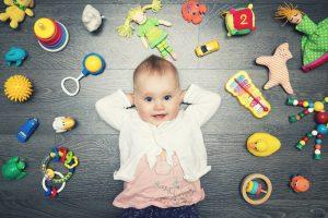 Kind ist umgeben von Babyspielzeug
