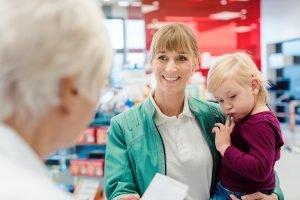 Mutter mit Kind in der Apotheke