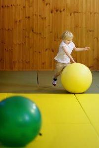 Kind rollt einen großen Ball