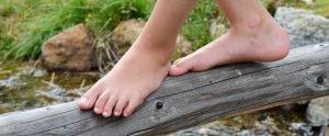 Mädchen balanciert mit nackten Füßen über einen dünnen Baumstamm