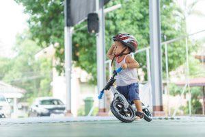 kleiner Junge auf einem Laufrad