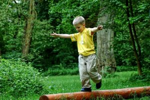 ein kind balanciert ueber einen baumstamm
