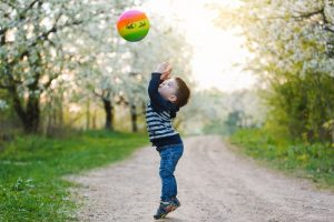 ein kleiner Junge spielt mit einem bunten Ball