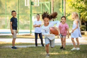 ein kleines maedchen rennt mit einem rugbyball ueber eine wiese