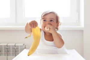 ein baby mit 1 jahr isst eine banane