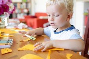ein Kind bastelt mit Schere und Papier
