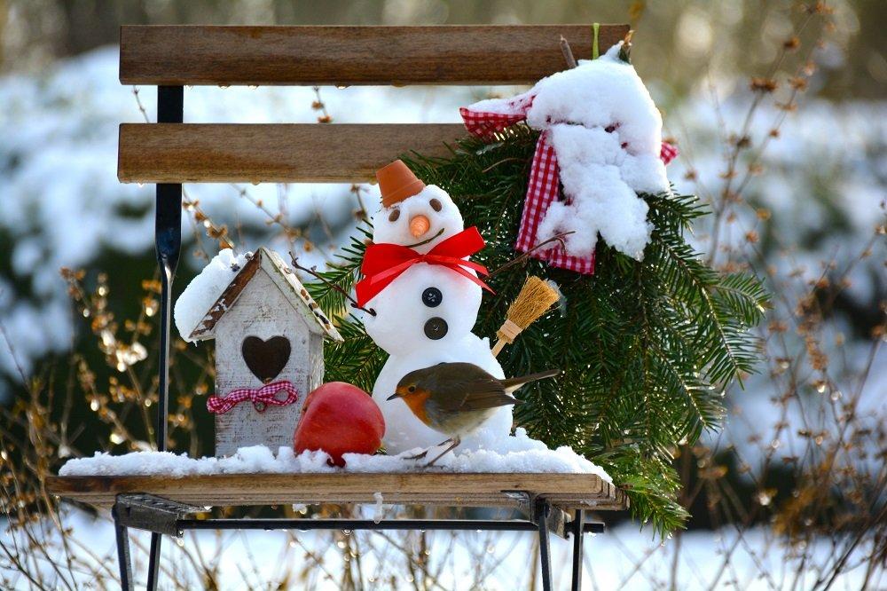 Schneemann mit Häuschen auf Holzstuhl