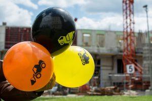 Luftballons mit Baustellensymbolen vor einer Baustelle im Hintergrund