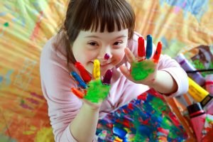 Ein Kind mit Trisomie 21 hält seine bemalten Hände in die Kamera