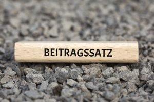 das Wort Beitragssatz auf einem Holzstück