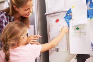 Mutter und Kind stehen vor einem Belohnungssystem