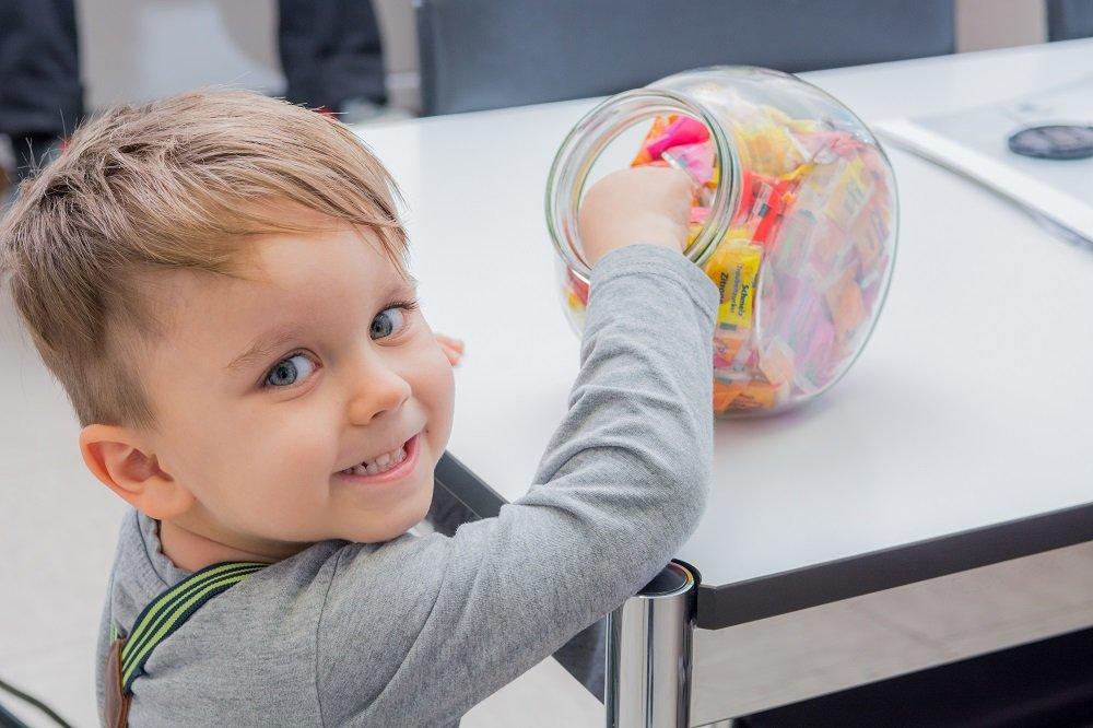 Kind nimmt sich Bonbons aus einem Glas