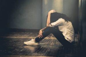traurige junge frau sitzt auf dem boden
