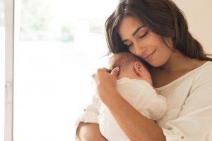 junge mutter haelt ihr baby fest im arm