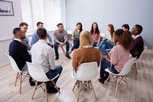 junge erwachsene sitzen zusammen in einem kreis