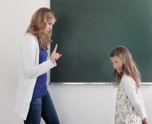 eine lehrerin steht mit erhobenem zeigefinger vor einer schuelerin