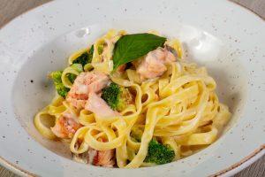 Brokkoli-Pasta mit Lachs auf einem weißen Teller