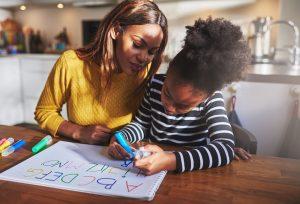 Mutter hilft ihrem Kind beim Buchstaben schreiben lernen