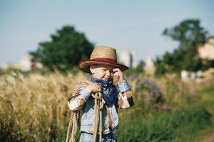 als Cowboy verkleideter kleiner Junge steht in einem Feld