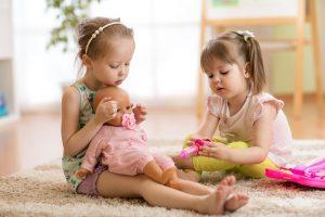zwei maedchen spielen mit einer puppe