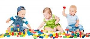 drei babys spielen mit baukloetzen