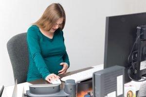 schwangere sitzt mit wehen am arbeitsplatz