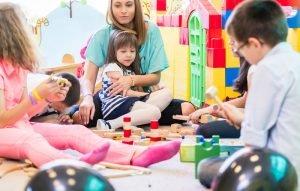 Kinder spielen zusammen auf dem Boden, Eine Mutter hält ein Kind im arm