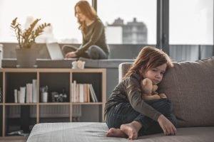 Kind sitz allein auf der Couch, während die Mutter am Laptop sitzt