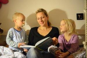 mutter liest ihren beiden kindern vor dem zubettgehen etwas vor