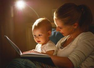 mutter liest ihrem baby aus einem buch vor
