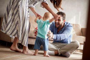 Glückliches Paar übt Laufen mit dem Kind