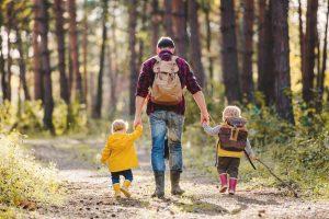 vater geht mit zwei kindern im wald spazieren