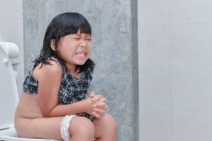kleines Mädchen sitzt mit Schmerzen auf Toilette