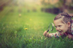 Mädchen liegt mit einer Lupe im Gras